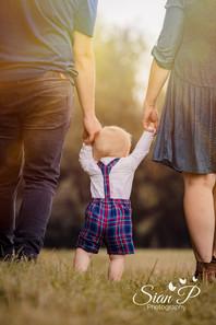 Toddler holding parents hands