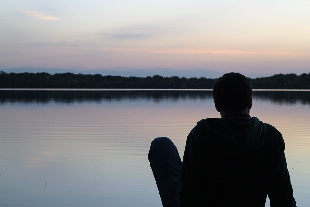 person looking at lake during sunset