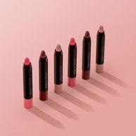 Dikke tube lippenbalsem in een diagonale compositie op een roze achtergrond.