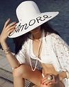 Fashion model wearing white swimwear, red nail polish, pearl necklace and a big white hat with 'amore' embroidered on it