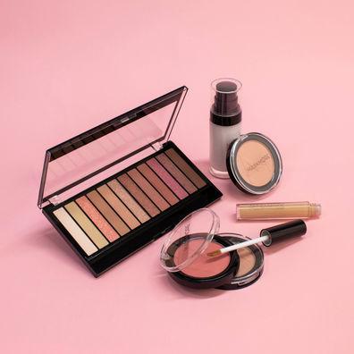 Compositie van oogschaduw, foundation en concealer gefotografeerd op een roze achtergrond