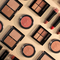Eyeshadow, blush and lipstick on a neutral background shot from above