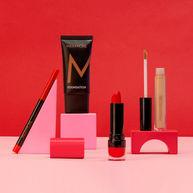 Speelse compositie met blokken en cosmetica met een rode en roze achtergrond