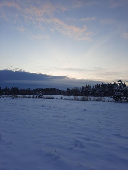 Talvinen maalaismaisema, jossa aurinko kajastaa pilvien takaa