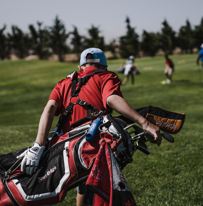 man-walking-carrying-black-and-red-golf-