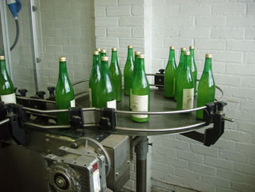 bottles of freshly pasteurised juice waiting to be packed