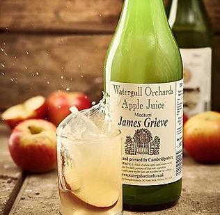 Apple Juice bottle and juice in glass splashing up