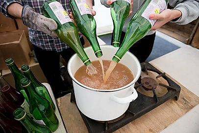 pouring mulled spiced apple juice in to a pan