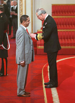 Honourable Chair receiving honour as MBE from Prince Charles on behalf of Her Majesty the Queen
