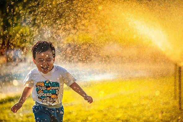 Boy Running Through Sprinker
