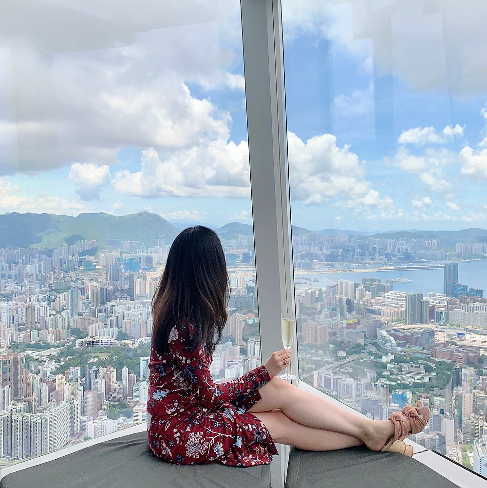 Jenni Lien of The Yay Project at Ritz Carlton Hong Kong looking at the view with a glass of champagne