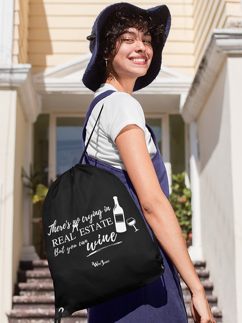There's no crying in real estate but you can wine - woman in front of house wearing a black drawstring bag with zipper pocket