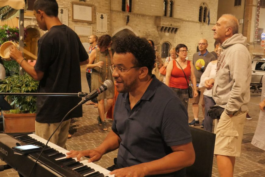 Luccas Soares, tocando teclado e cantando em uma praça com diferentes pessoas ao redor.