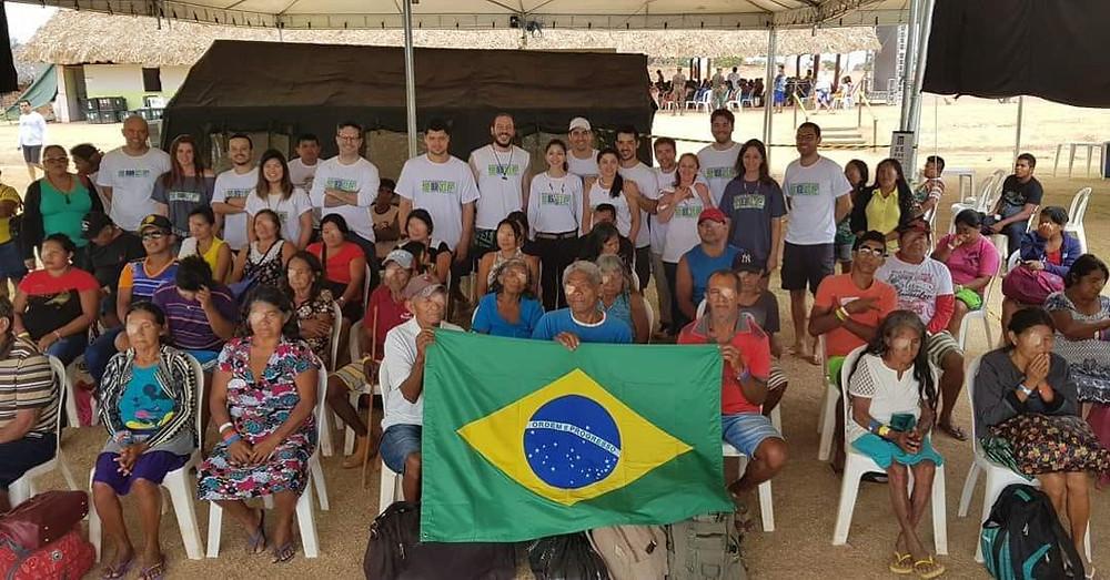 Equipe da EDS com população atendida segurando uma bandeira do Brasil