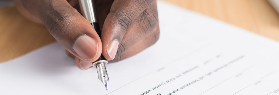 A black hand holding a pen signing a leasing contract