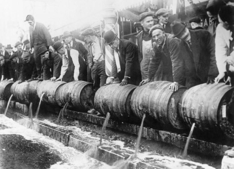 大量のお酒を廃棄する人々