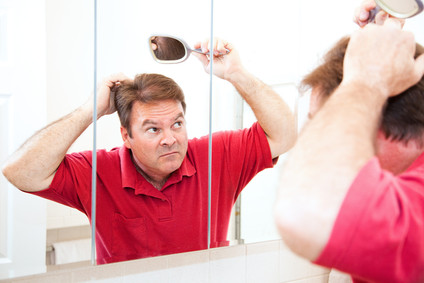 Man in Mirror looking at hair