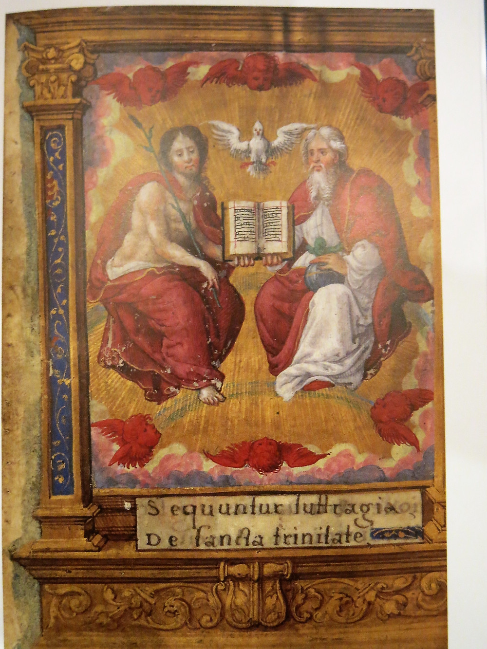The Father and Son seated with a book between them over which the dove hovers