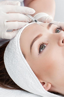 Woman receiving Botox injection to her forehead.