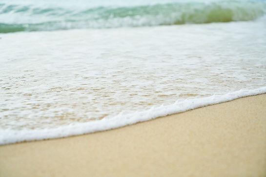calm sea foam rolling onto sand