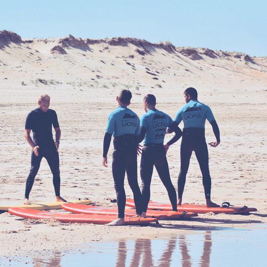 Ecole de Surf de Guadeloupe  Explication du bon postionnement du corps sur la planche avant de retourner à l'eau pour le continuer le cours de surf (UCPA Soustons - Août 2018)