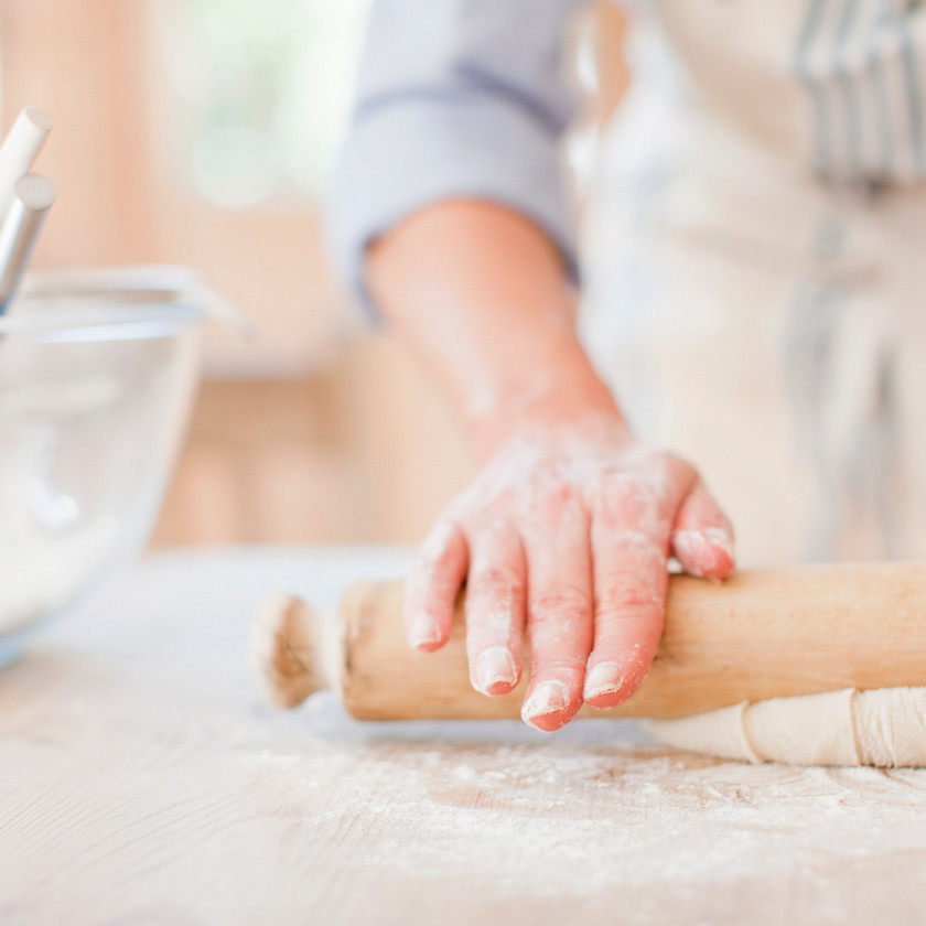 Woman rolling out dough using a rolling pin.