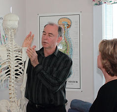 Dr. Philip LaPierre demonstrates for a patient how he will be treating her shoulder