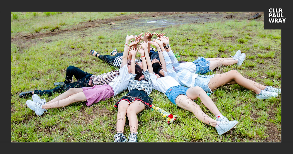 Young people laying on field of grass with their hands in the air.