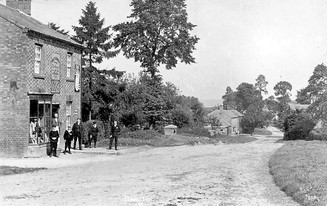 Group of people standing outside village shop in Ilmington. 1900s