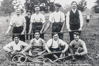 Tug of war team at Foxcote fete 1925(?). Top row: Jim Baker (Blockley or Ebrington), Jack Cooke, Bill Cooke, ?. Bottom row: Sid Cooke, Fred Dumbleton,?, ?. George Cook in background