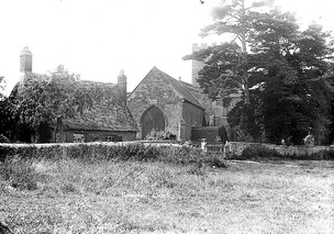 St Mary's church, Ilmington. There is a small thatched cottage to the left and a girl standing at the church gate. 1900s