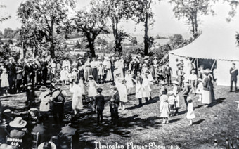 Ilmington flower show 1919. Sam Bennett, playing the fiddle (left side of the photo) and some of his 'morris dancers' - the girls in white dresses.
