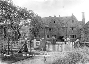 The Manor House, Ilmington. A lady is sitting astride a horse in front of the house. 1900s