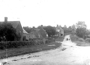 A woman and three children walking up Foxcote Hill, with cottages to the left. 1900s