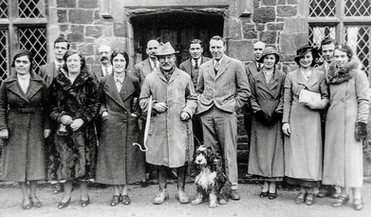 """The Empire broadcast, Christmas day 1934. Back row (L-R): Frank Mayo, George Cook (church organist), Frank Boswell (landlord of Red Lion), George Hands (chauffeur at the Manor), Will Venables, Tom Cook. Front row (L-R): Mrs Kit Freeman, Mrs Bessie Faulkner (who had a wonderful contralto voice), Mrs Amy Robotham (Mr Mayo's sister), Walton Handy (the Cotswold shepherd), Spenser Flower (the """"Major"""" and compere of the event), Mrs Ethel Bennett, Miss Gwennie Smith, Miss Freda Bryan. Dog's name not known"""
