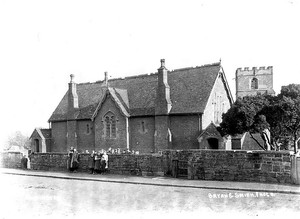 Ilmington village school with pupils standing by wall. 1900s