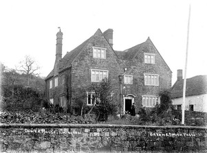 Exterior of the Dower House, Ilmington. A man and woman are standing in the garden. 1900s