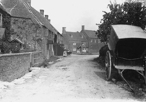 Middle street, Ilmington, showing cottages, woman with pram, delivery cart (no horse). 1900s