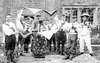Ilmington Morris Men with handkerchiefs, Ilmington. 1900s [The Morris Men are dancing 'Maid of The Mill' unique to the Ilmington morris dance tradition as a linked handkerchief dance.The musician is Sam Bennett, fiddle player who died in 1951 aged 85 years. The dance is still danced to this day by the current Ilmington Morris dancers, who usually dance around the local villages on a Wednesday evening from May to August]