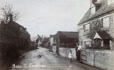 Woman with two children standing in front of a cottage in Middle Street, Ilmington. 1910s