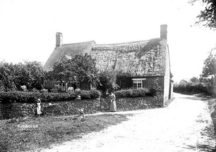 Thatched cottage, with woman and children at gate, Ilmington. 1900s