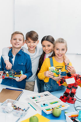 Children in a STEM classroom building robots