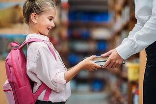 Child receiving books from a teacher