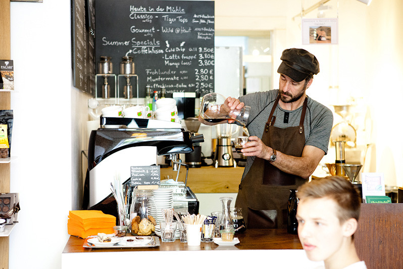 Barista (Jörg) preparing coffee for a customer in Elephant Beans Coffee.