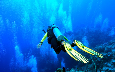 A diver is in 'free fall' position, gliding over the edge of an abyss that drops to 6000 ft! Shot on the wall of Grand Cayman against a back