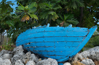 Wreck small blue Catboat in a street of Grand Cayman, Cayman Islands