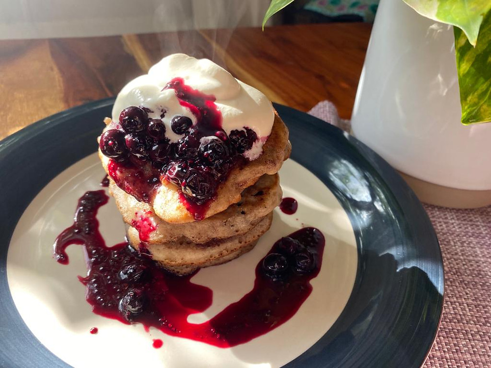 Gluten free blueberry pancake stack with blueberry compote and whipped cream