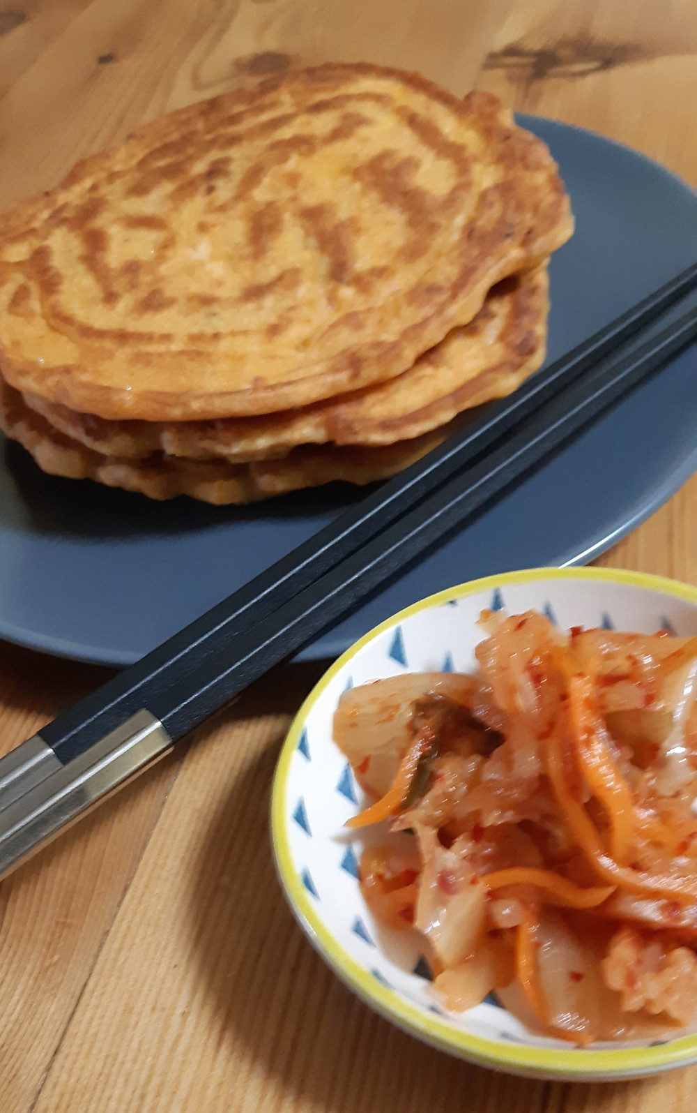 Kimchi pancakes in the background with small serving of kimchi