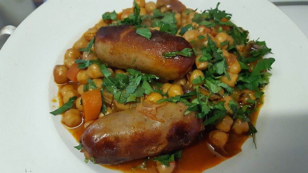 A plate of serving of chickpeas that have been braised with smoked paprika, vegetables and sausages, topped with fresh parsley