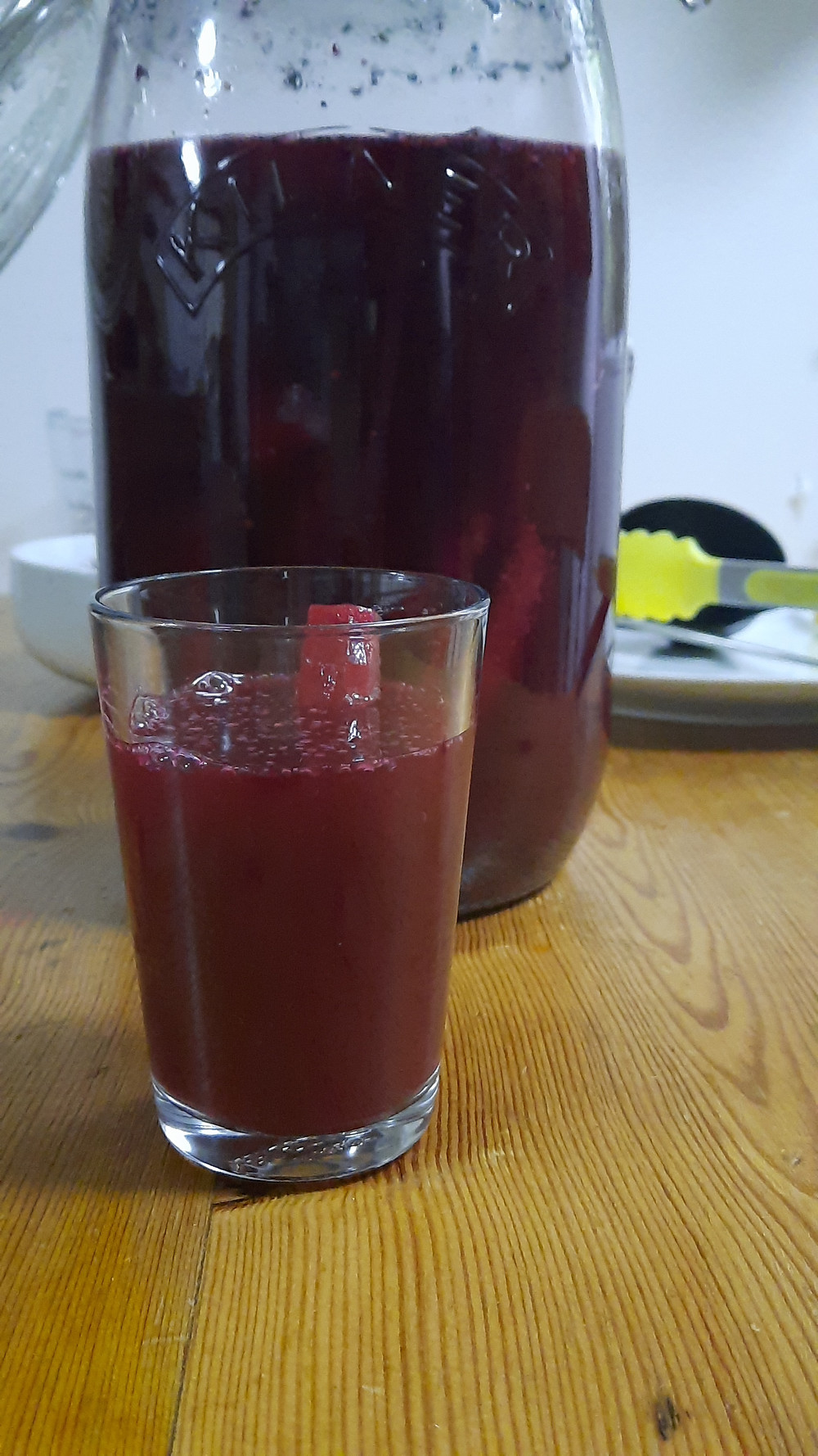 Glass of kanji with purple carrot stick and kanji in container in back ground